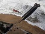 A la mi-journée, une moitié du navire était encastrée contre une digue (photo), et l'autre moitié était quasiment échouée sur le rivage, balayé par une très forte houle. (Regis Duvignau / Reuters)